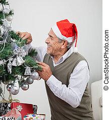 Man Wearing Santa Hat Decorating Christmas Tree - Smiling...