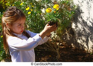 Young girl planting flowers in the garden. - Young girl...