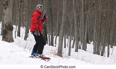 Snowboarder practicing in a winter forest