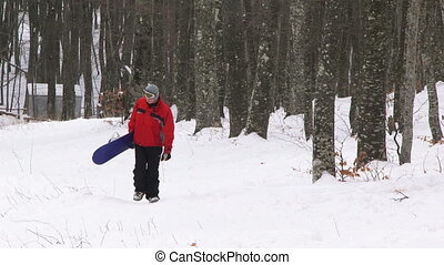 Tired snowboarder walking in a forest with his board