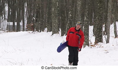 Snowboarder in a forest - Snowboarder walking in a winter...