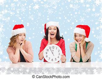 women in santa helper hats with clock showing 12 -...