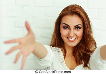 Young cheerful woman with hands open trying to reach the camera