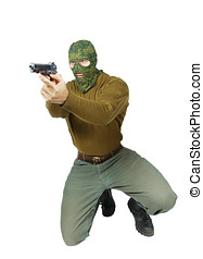 Man wearing camouflage mask is aiming with a pistol