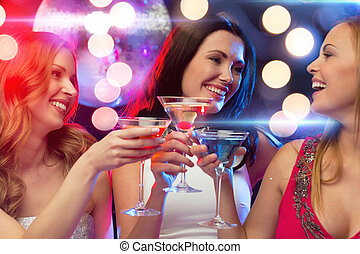 three smiling women with cocktails and disco ball