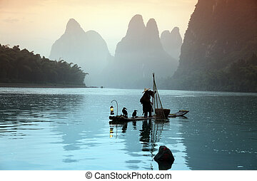 Chinese man fishing with cormorants birds in Yangshuo,...