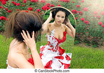 a beautiful young girl in a red dress straightens her hair...