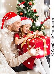 smiling father and daughter opening gift box - family,...