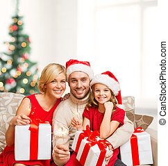 smiling family holding gift boxes and sparkles - family,...