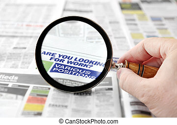 Looking for Work - Magnifying glass over a newspaper job...