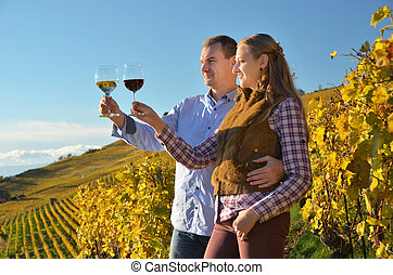 Man and woman tasting wine among vineyards in Lavaux,...