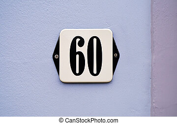 Number 60 - House Number Sixty-two sign at a plastered blue...