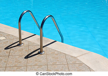 railing stairs in the blue swimming pool