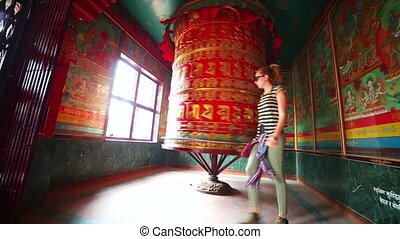 Caucasian tourist girl spinning at Prayer wheel