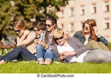 students looking at smartphones and tablet pc - education,...