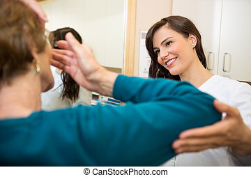 Optometrist Assisting Woman To Insert Contact Lens - Female...