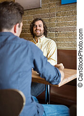 Man With Friend Sitting At Coffeeshop - Portrait of happy...