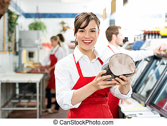 Happy Female Butcher Holding Large Ham - Portrait of happy...