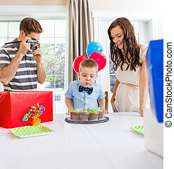 Boy Blowing Out Candles On Cake At Home - Father taking...