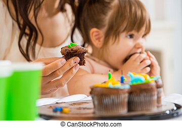 Mother Holding Cupcake With Girl Eating Cake