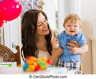 Mother Holding Baby Boy At Birthday Party - Happy mother...