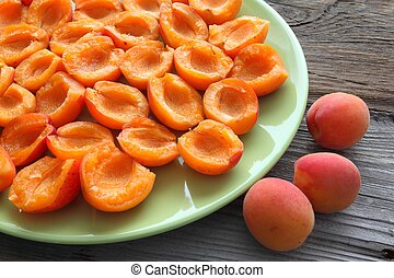 Apricots - Apricot halves on a green plate. Ripe fruit.