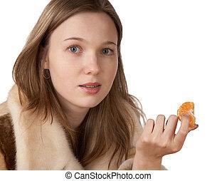 The girl in a fur coat holds segment of tangerine on white...