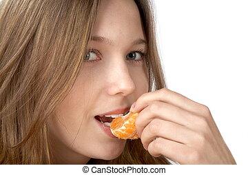 The girl  eats  tangerine on  white background