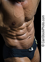 Detail of bodybuilder torso: ripped abs and pecs - Detail of...