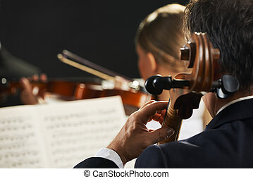 Classical music - Symphony, cellist on foreground playing at...