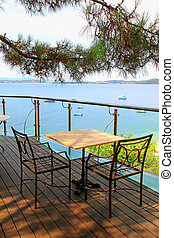 Table and iron chairs on terrace with sea view (Greece) -...