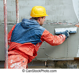 Builder at facade plastering works