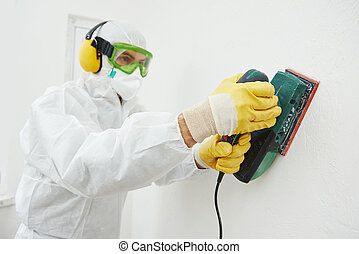 worker with sander at wall filling - Home improvement worker...