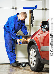 auto mechanic at car headlight checkup - car mechanic...