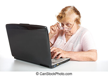 The old woman in glasses looks at the screen notebook on a...