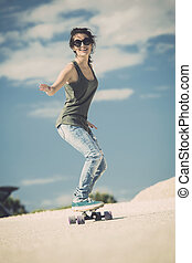 Skater Girl - Young woman down the road with a skateboard