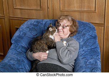 The grandmother with a cat in house conditions