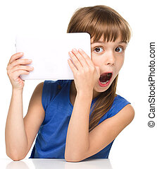 Young girl is using tablet while sitting at table, isolated...