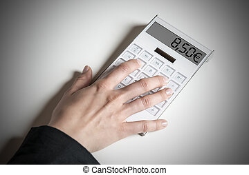 Calcluator indicating 8.50€ - Female hand with calculator,...