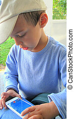 Toddler playing game on iphone - Toddler with cap playing...