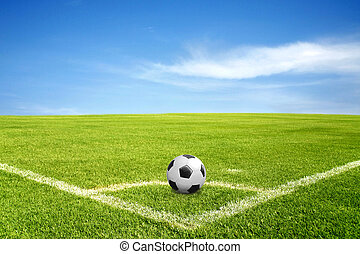 a ball on corner of football field in green grass with blue...