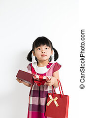 Toddler girl with gift box and bag