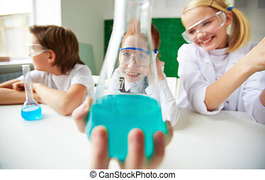 Having fun - Happy schoolgirl holding tube with chemical...