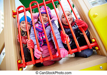 Friends on playground - Happy kids in winterwear having fun...
