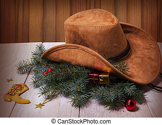 Cowboy western hat and Christmas decoration on wood...