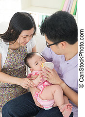 chinese asian parents feeding baby boy at home