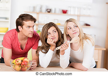 Three young friends undecided on what to cook leaning on a...