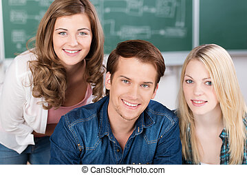 Handsome young male college student sitting at a desk...