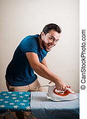 young stylish man housewife ironing at home