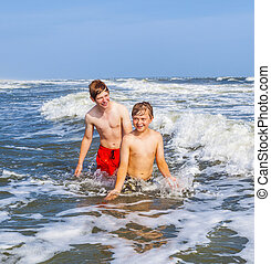 boy enjoying the beautiful ocean and beach - boys having fun...